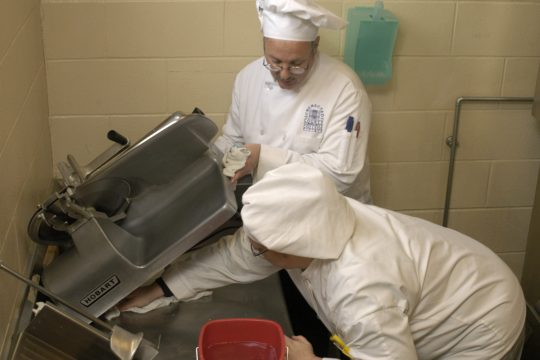 Schenectady County Community College culinary student Rebecca Rivera cleans under a deli slicer as Chef Dave Wixted lifts it off the counter on Monday.