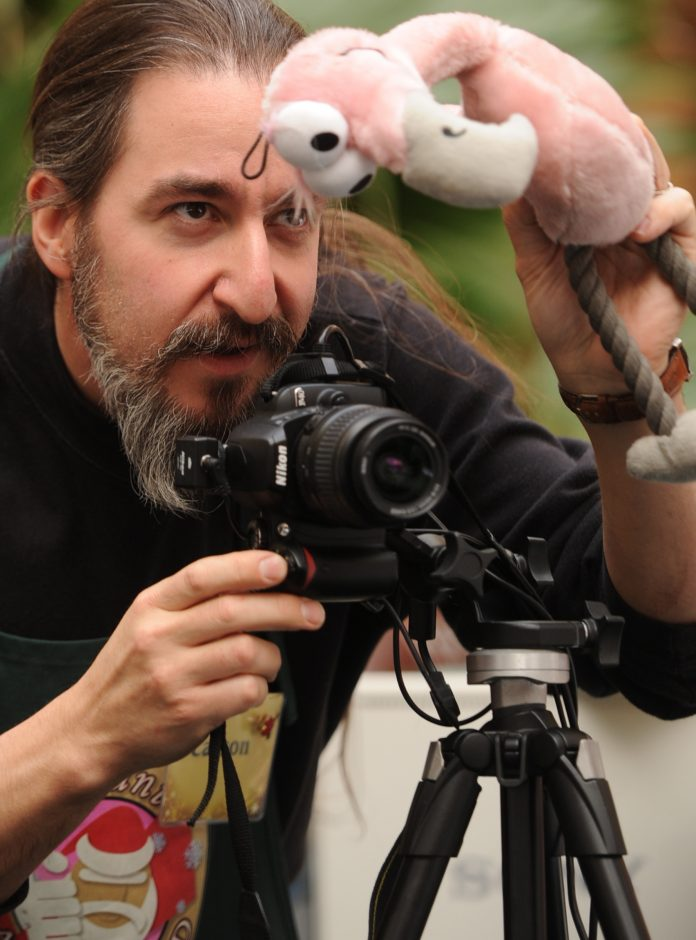 Jonathan Ment tries to get a child's attention with a stuffed flamingo toy while photographing a visit to Santa.