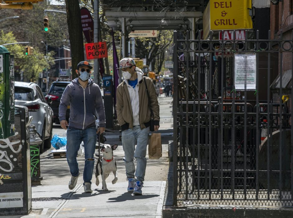 Two men wearing protective face masks walk with a dog in New York City on Wednesday, April 15, 2020.