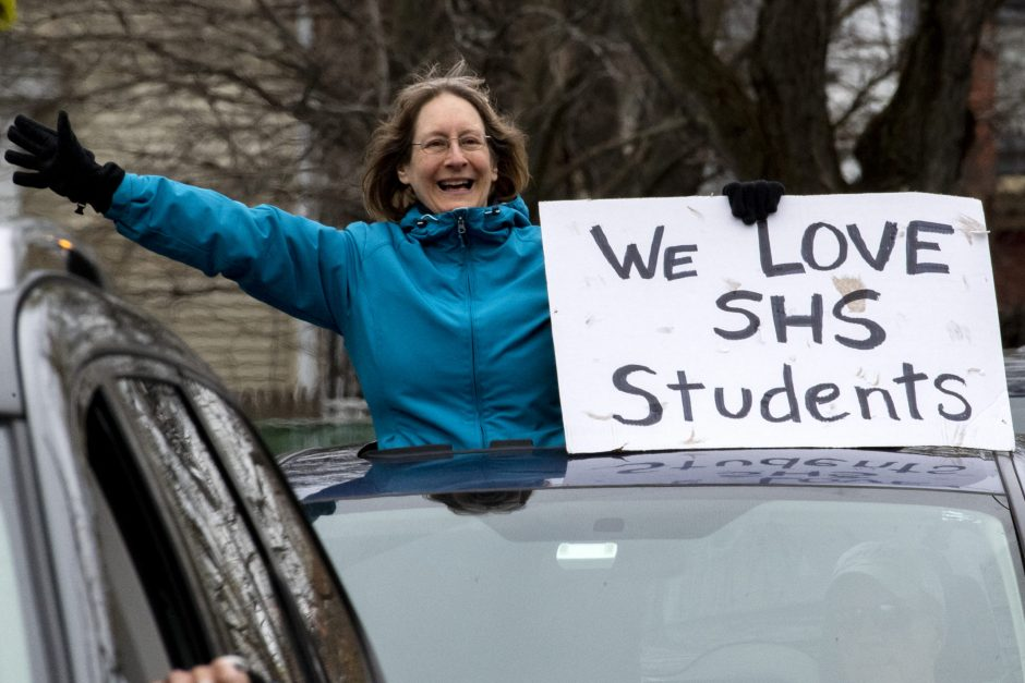 Retired Schenectady School District teacher Mary Weddis holds up a sign on Park Street in Schenectady Friday.