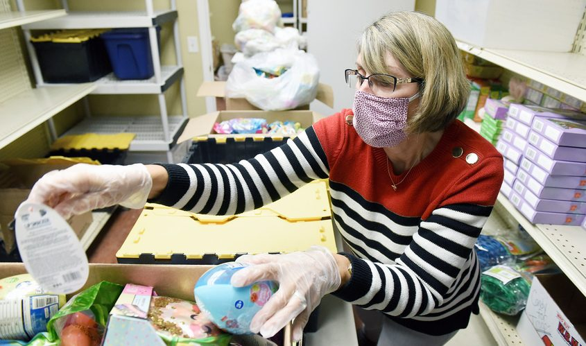 Operation Adopt A Soldier Volunteer Mary Duxbury, of Milton, sorts and stacks candy donated by Walgreens Thursday