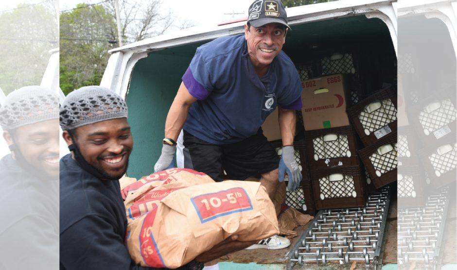 Steven Rivera, right, offloads potatoes to Jamar Vanmorter Friday morning at the Amen Place Soup Kitchen on Guy Park Ave.