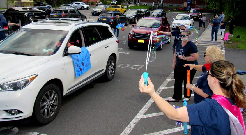 Vans, cars and sports utility vehicles cruise through the parking lot at St. Kateri Tekakwitha Parish School Saturday
