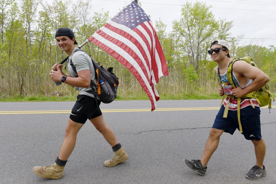 Jack Trimmings, left, and Vincent Sablich walk on Gilbert Road with 40-pound weights to honor fallen soldiers.