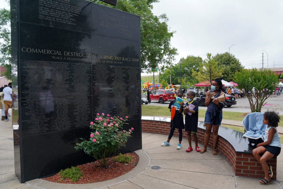 People study the 1921 Black Wall Street Memorial during the Juneteenth celebrations in Tulsa, Okla., on Friday, June 19, 2020.