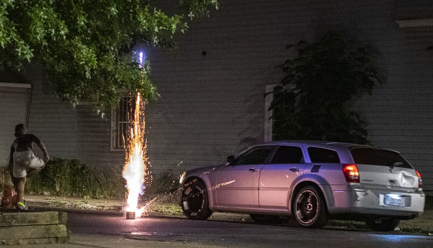 A car passes an exploding firework at the intersection of Backus and Albany streets June 23