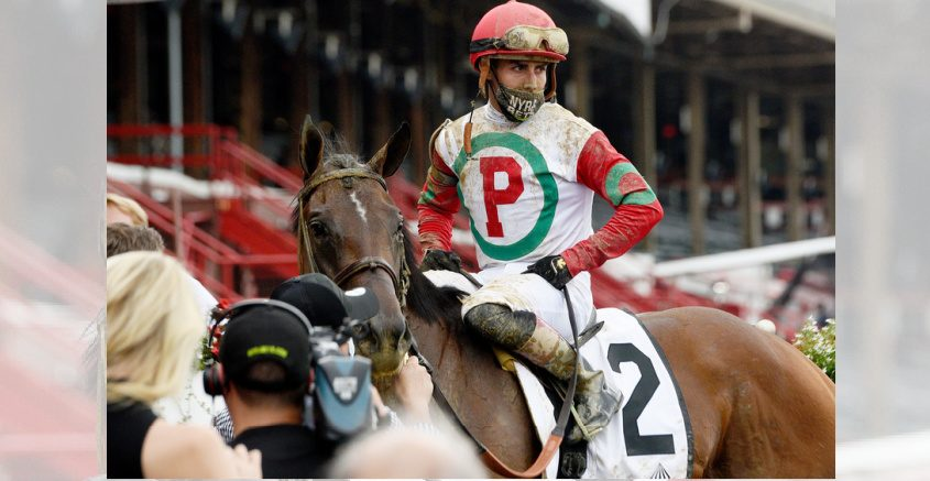 With an empty grandstand as a backdrop, jockey Irad Ortiz poses with Peter Pan winner Country Grammer.