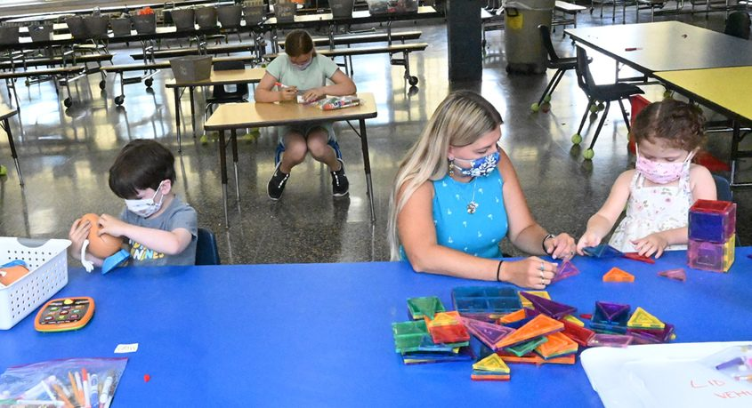 Renee Unger, teaching assistant, works with young Emma Ritz during the Brown School Summer Program.