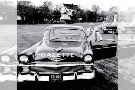 Charles B. Sellers Jr. stands beside the Schenectady Gazette's photo car as other photo staffers are shown in the background.