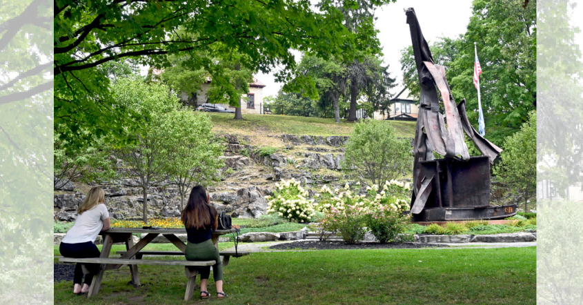 Two people sit at a picnic table in front of the Sept. 11 Memorial on High Rock Street in Saratoga Springs Thursday. Photo by Marc Schultz/Staff Photographer